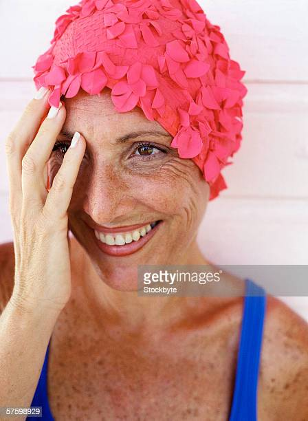 close-up of an elderly woman wearing a swimming suit and cap and hiding her face