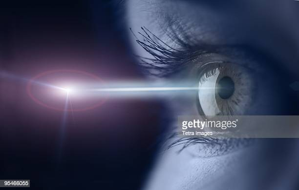 Close-up of an eye with a light beam shining into it