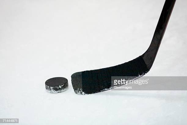 Close-up of an ice hockey stick with a hockey puck