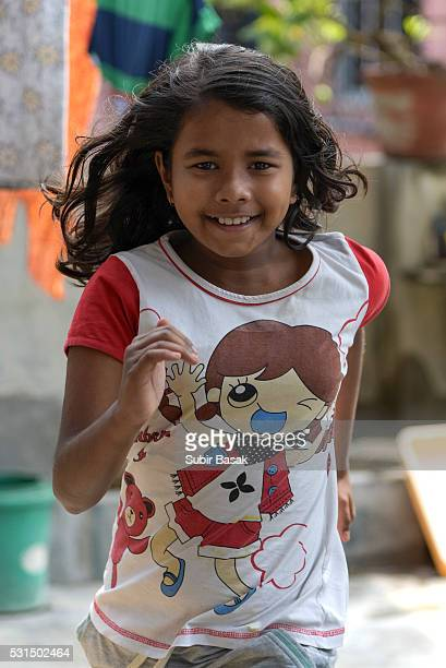 Close-up of an Indian girl running with smile.