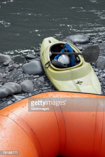 Close-up of an inflatable raft and a kayak at a riverbank : Stock Photo