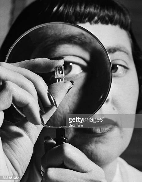 Closeup of an RCA lab technician using a magnifying glass to inspect a new transistor the revolutionary electronic amplifier