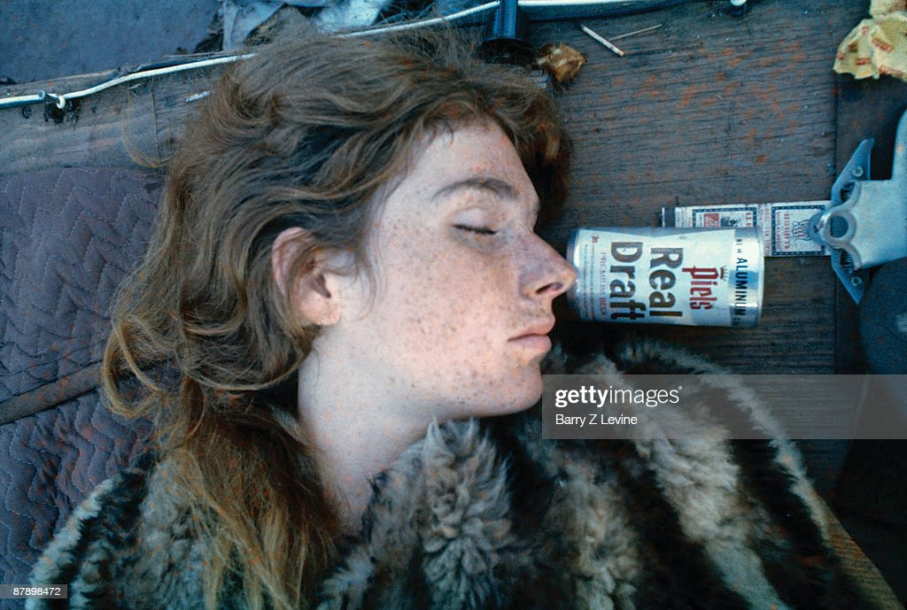 Close-up of an unidentified concert-goer asleep outdoors, next to a can of beer, at the Woodstock Music and Arts Fair in Bethel, New York, August 15 - 17 (and part of the 18th), 1969.
