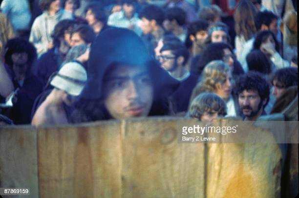 Closeup of an unidentified festivalgoer as he stands behind a wooden fence blurred by a cloud of smoke at the Woodstock Music and Arts Fair in Bethel...