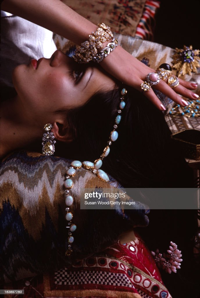 Close-up of an unidentified model dressed in costume jewelry as she reclines on embroidered cushions, September 1968. The image was taken during a fashion shoot for British Vogue magazine.