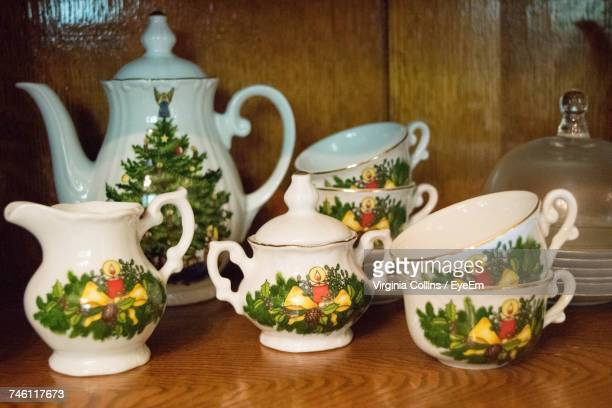 Close-Up Of Antique Tea Cups And Teapots In Table