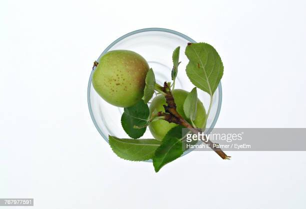 Close-Up Of Apple In Bowl Against White Background