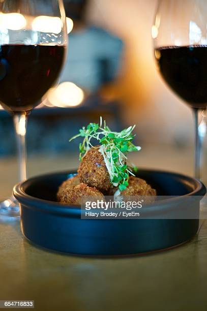 Close-Up Of Arancini Served With Red Wine On Table