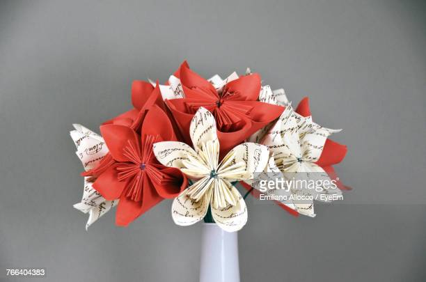Close-Up Of Artificial Flowers In Vase Against Gray Background