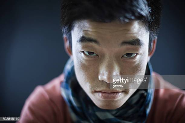 Close-up of Asian boy looking at camera with fixed gaze.