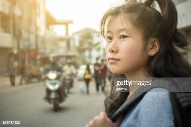 Close-up of Asian girl on city street.
