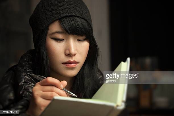 Close-up of Asian girl student writing in a notebook.