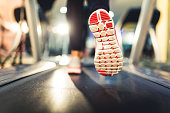 Woman running on treadmill, close up on shoes