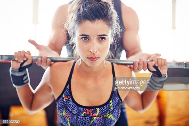 Close-up of attractive woman lifting barbell while coach assisti
