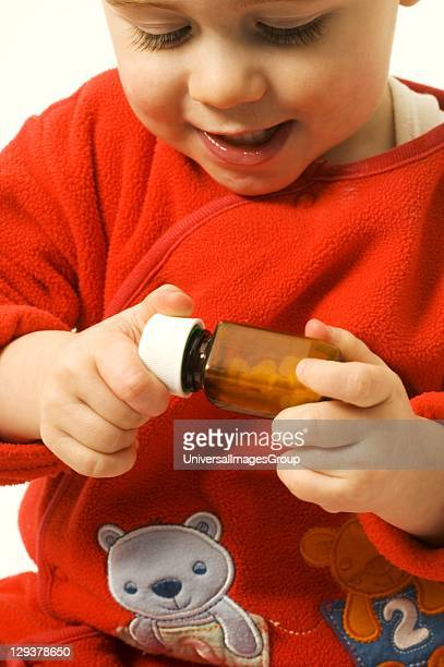 Closeup of baby boy trying to open medicine bottle