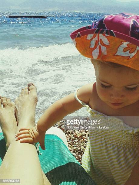 Close-Up Of Baby Girl With Woman Leg On Deck Chair