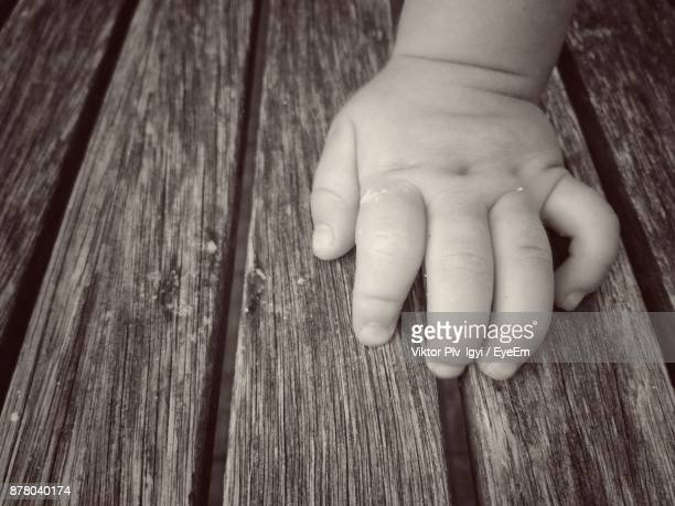 Close-Up Of Baby Hand On Wood