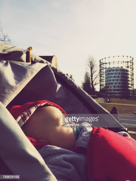 Close-Up Of Baby With Pacifier In Mouth Sleeping Against Sky At Park
