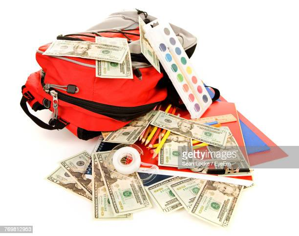 Close-Up Of Bag And Paper Currencies Over White Background