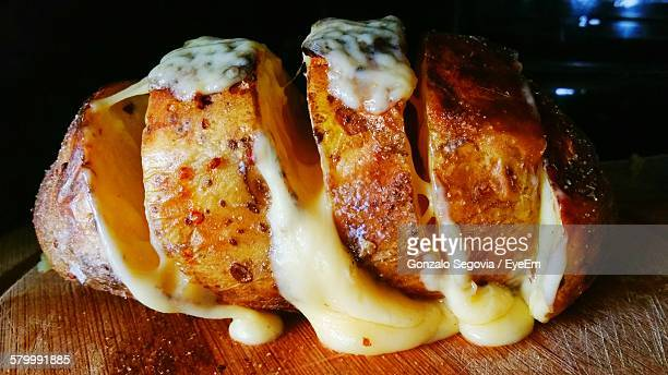 Close-Up Of Baked Potato With Cheese On Cutting Board