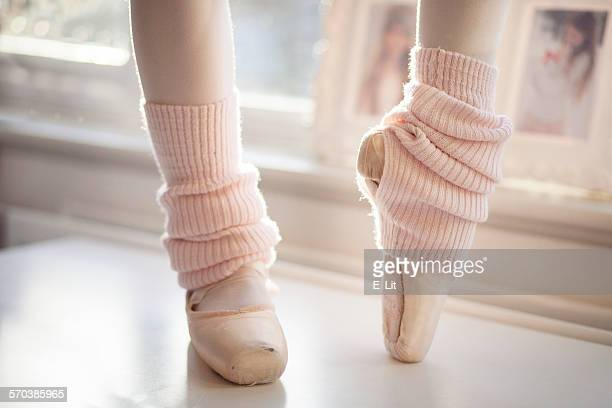 Close-Up of Ballerina Feet in Pointer Shoes and leg warmers