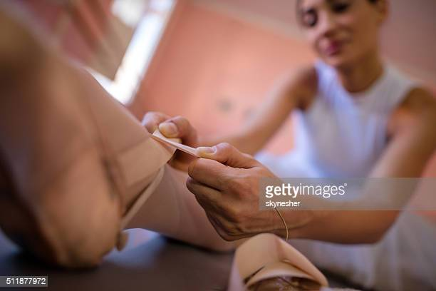 Close-up of ballerina tying up her ballet pumps.