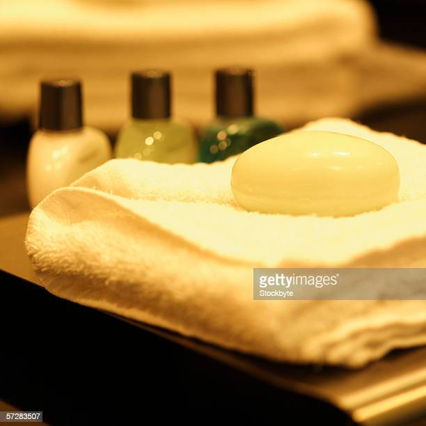 Close-up of bar of soap on towel with bottles of lotion in the background