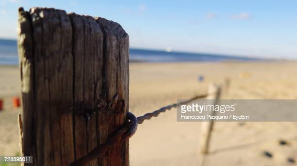 Close-Up Of Barbed Wire On Wooden Post At Beach Against Sky