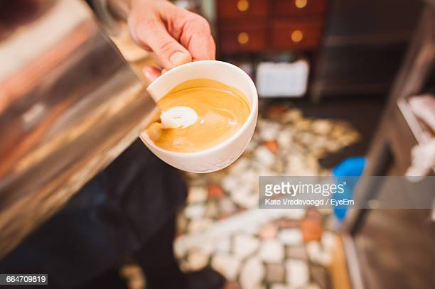 Close-Up Of Barista Pouring Cream In Coffee At Cafe