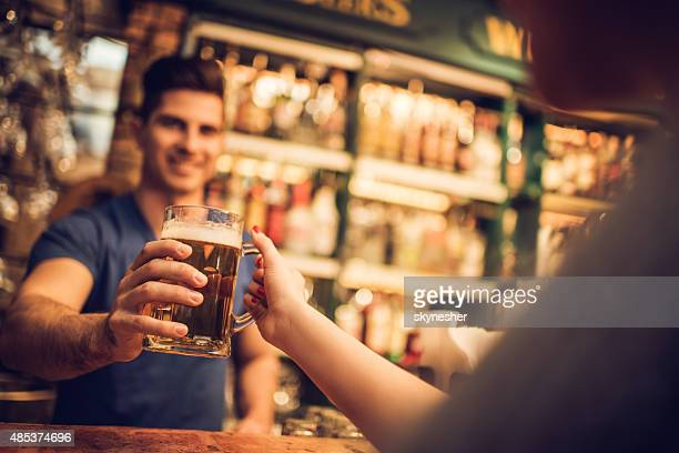 Close-up of bartender giving beer to a customer in bar.