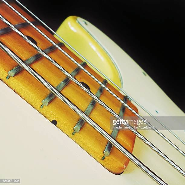 Close-Up Of Bass Guitar Against Black Background