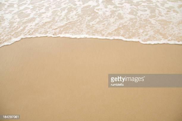 Close-up of beach coastline with receding waves