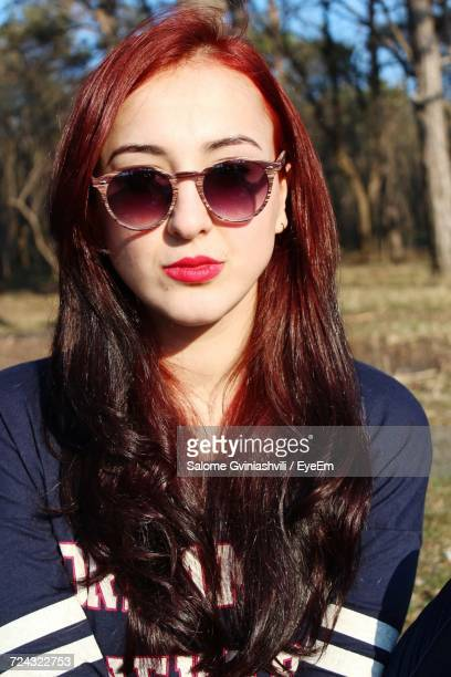 Close-Up Of Beautiful Young Woman With Long Brown Hair Wearing Sunglasses