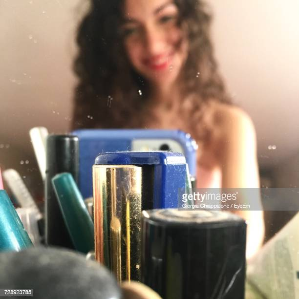 Close-Up Of Beauty Products Against Woman Reflecting On Mirror