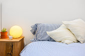 Bed, pillows and bedside table with lamp