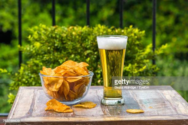 Close-Up Of Beer And Potato Chips On Table At Yard