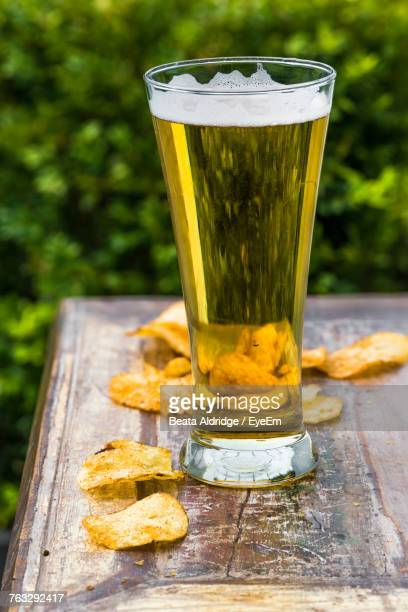 Close-Up Of Beer And Potato Chips On Table