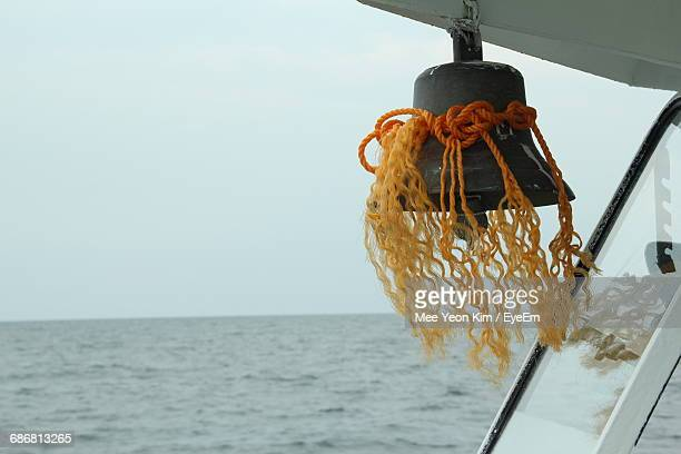 Close-Up Of Bell Hanging On Boat Against Clear Sky