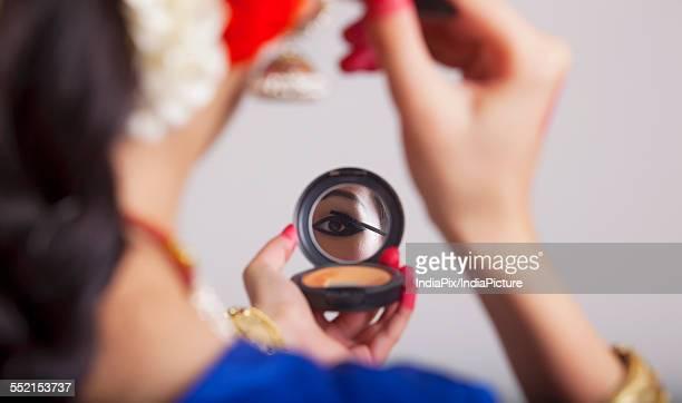 Close-up of Bharatanatyam dancer applying mascara over gray background