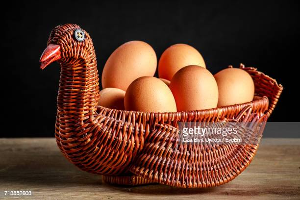 Close-Up Of Bird-Shaped Basket With Eggs Against Black Background