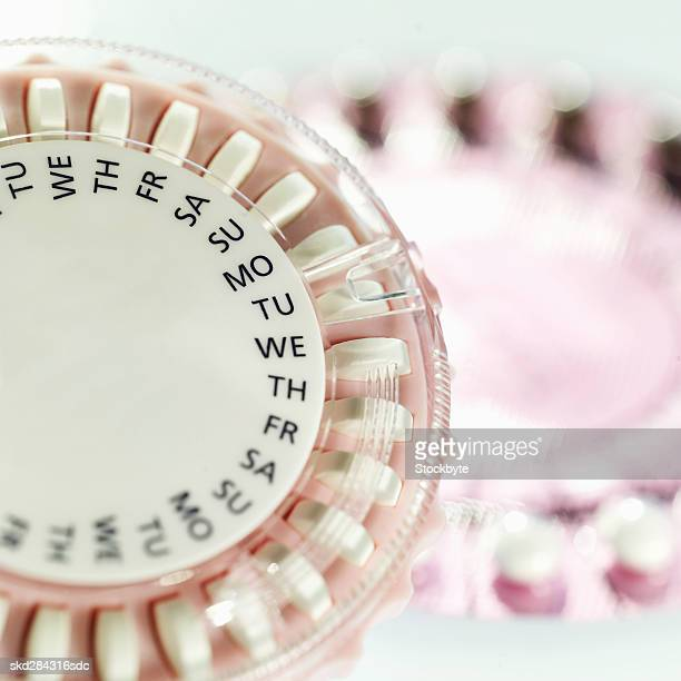 Close-up of birth control pills in two plastic tablet dispenser cases