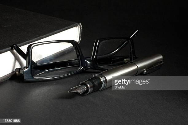 Close-up of black glasses next to a black book and pen