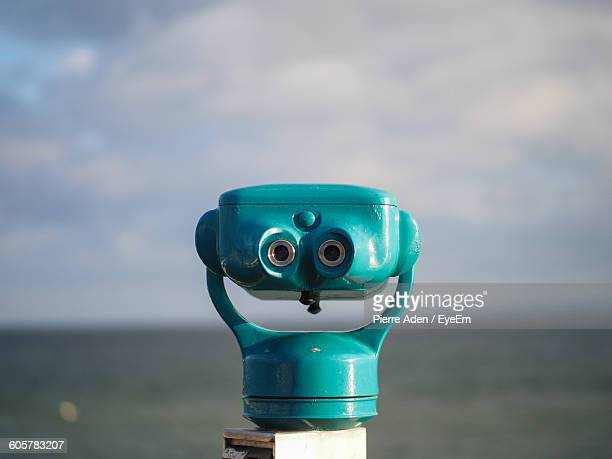 Close-Up Of Blue Coin-Operated Binoculars Against Sea On Sunny Day