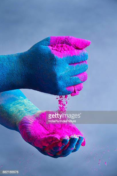 Close-up of blue colored hands holding pink powder paint