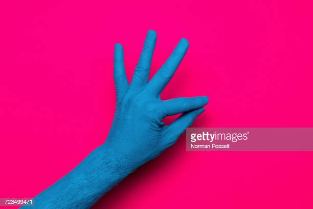 Close-up of blue painted hand gesturing OK sign against pink background