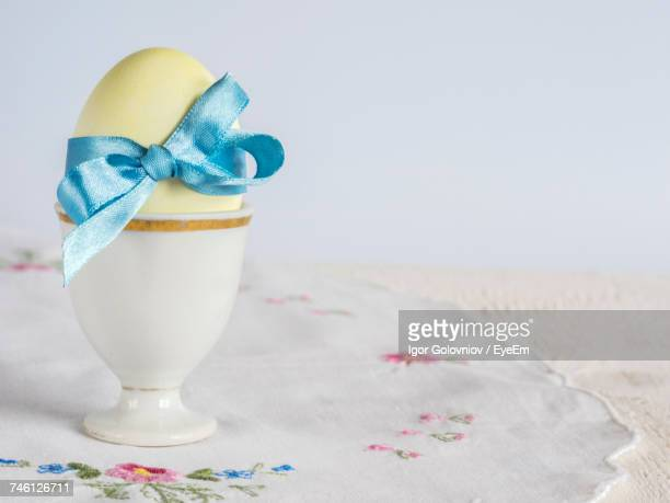 Close-Up Of Blue Tied Bow Ribbon On Easter Egg On Table