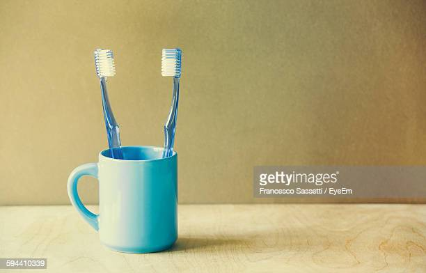 Close-Up Of Blue Toothbrushes In Cup On Table Against Wall