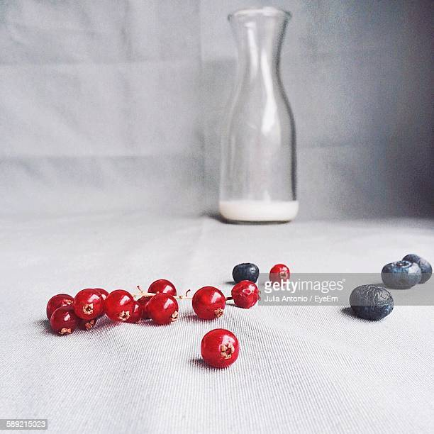 Close-Up Of Blueberries And Redcurrants With Milk Bottle On Table