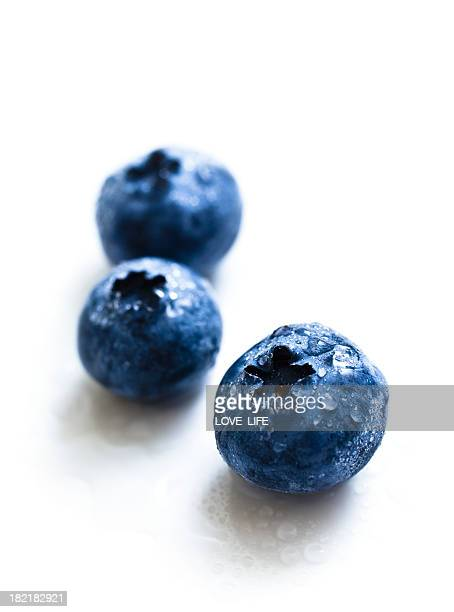 Close-up of blueberries with water drops on white background