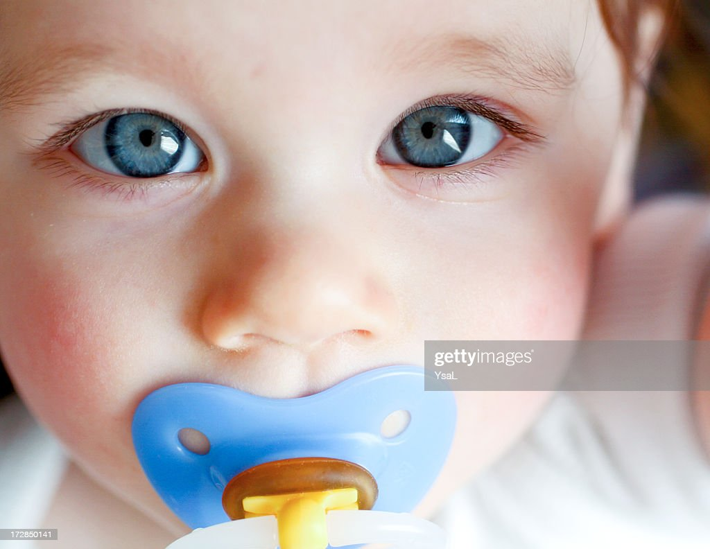 Close-up of blue-eyed baby with blue pacifier : Stock Photo
